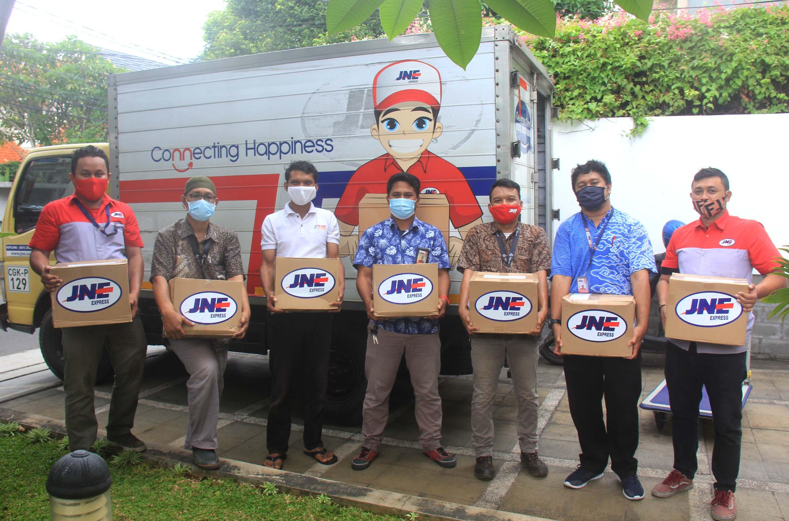 Tim JNE dan pihak Klinik Mata Alla saat serah terima donasi ribuan Al Quran