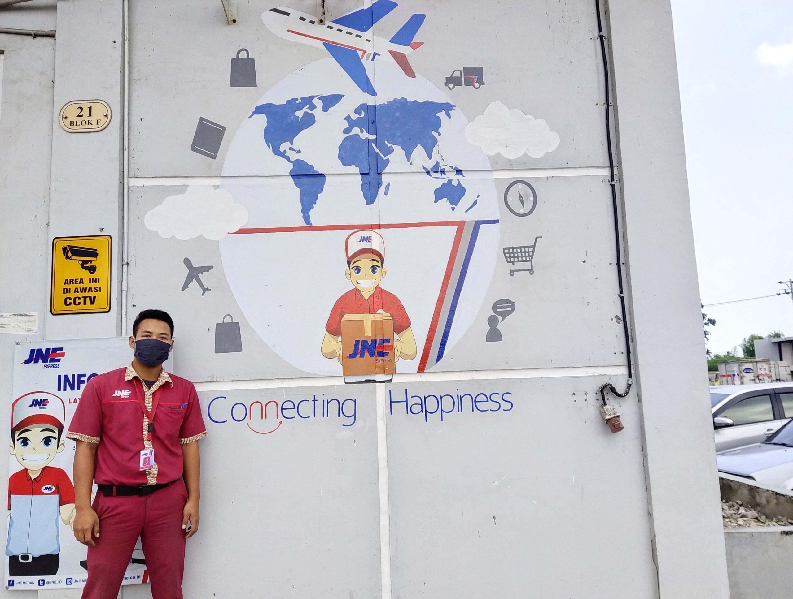 Ksatria Abdihil Mukhlis dengan hasil karya lukis muralnya di dinding gedung JNE Medan