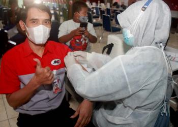 Arianto, karyawan JNE dari JNE Hub Garuda, Kemayoran, Jakarta Pusat, tengan menerima suntikan dosis kedua.